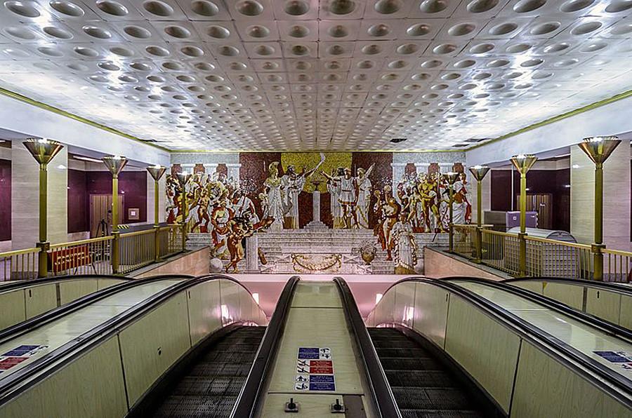 Hall superior da estação Sportívnaia decorado com atletas e deuses gregos.