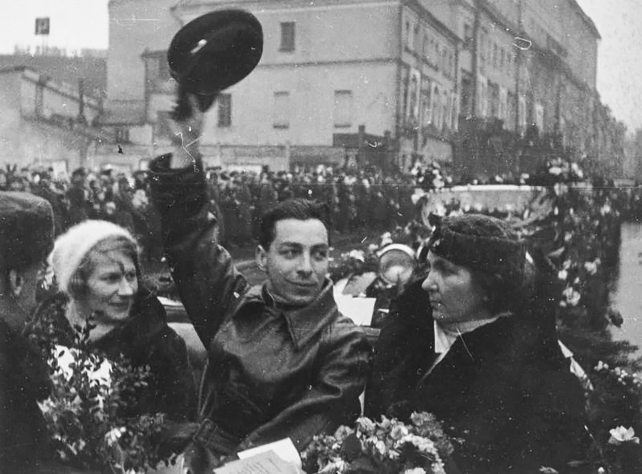"""Јевгениј Фјодоров у аутомобилу. Дочек Папањинових хероја у Москви. Данас је ово Мјасњицка улица у Москви. Станица """"Северни пол 1"""" званично је отвоена 6. јула 1937. Девет месеци касније, након 274 дана плутања према југу, станица се нашла у Гренландском мору. Санта леда је превалила преко 2.000 км."""