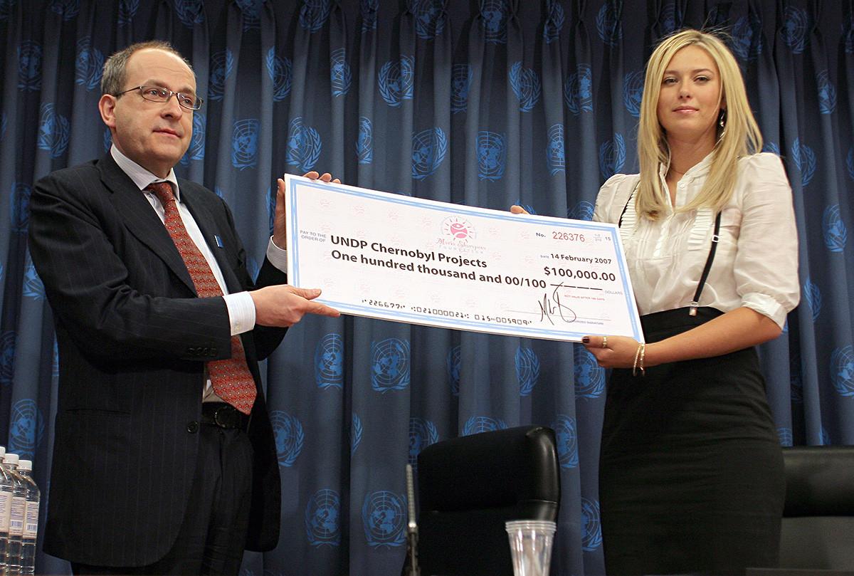Ad Melkert, pomožni administrator UNDP prejema ček od Marije Šarapove med tiskovno konferenco, na kateri je bila ruska športnica razglašena za ambasadorko dobre volje Združenih narodov, 14. februarja 2017.