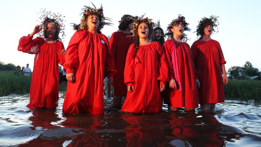Jóvenes caminan en el agua durante la celebración del día de Iván Kupala.