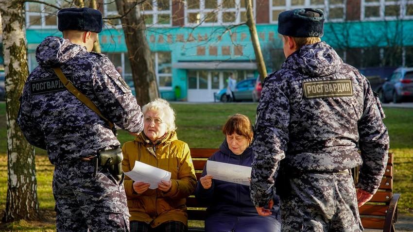 Soldados da Guarda Nacional da Rússia falam com idosos em Moscou.