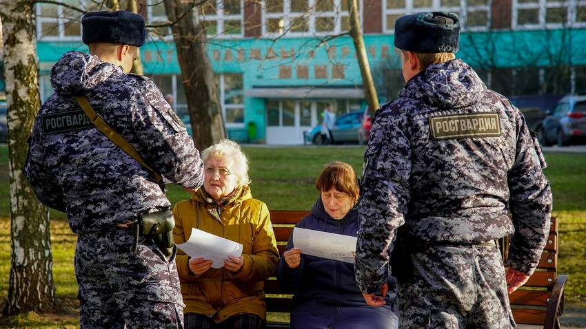 Rosguardia soldiers speak to two pensioners in Moscow.