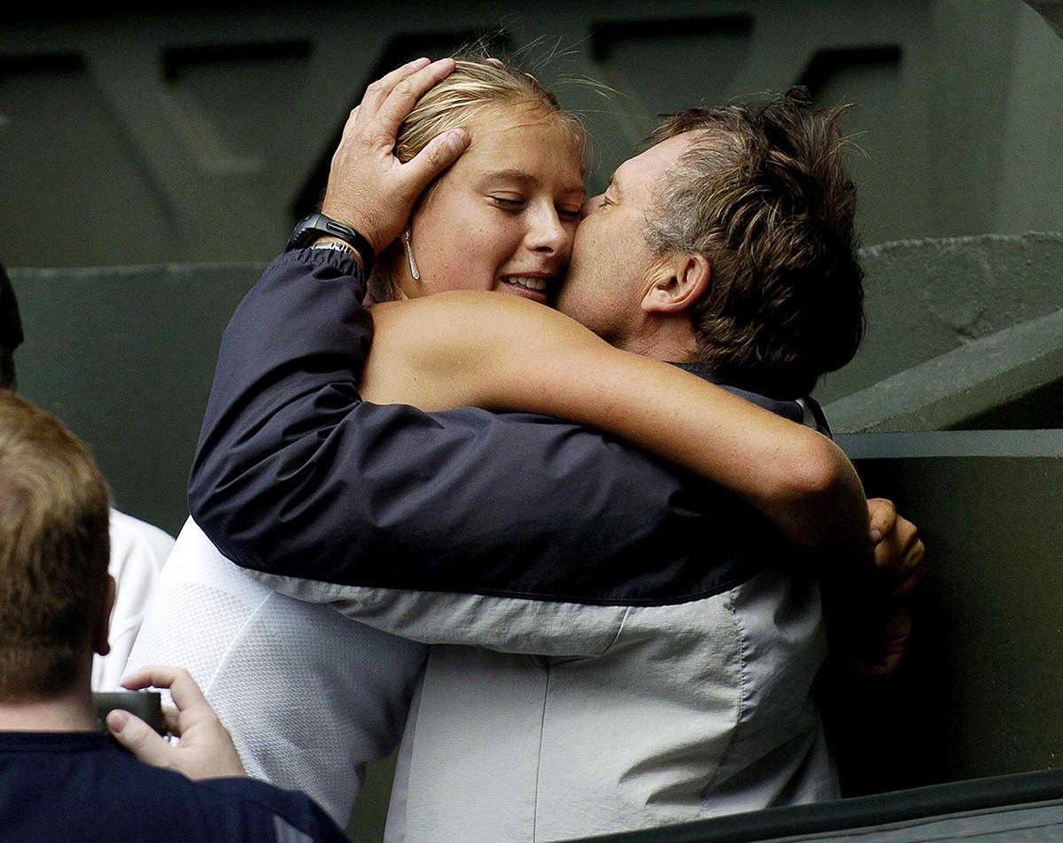 Maria Sharapova berpelukan dengan ayahnya Yuri Sharapov setelah mengalahkan Serena Williams di final turnamen Tunggal Putri pada Kejuaraan Tenis Rumput di Wimbledon.
