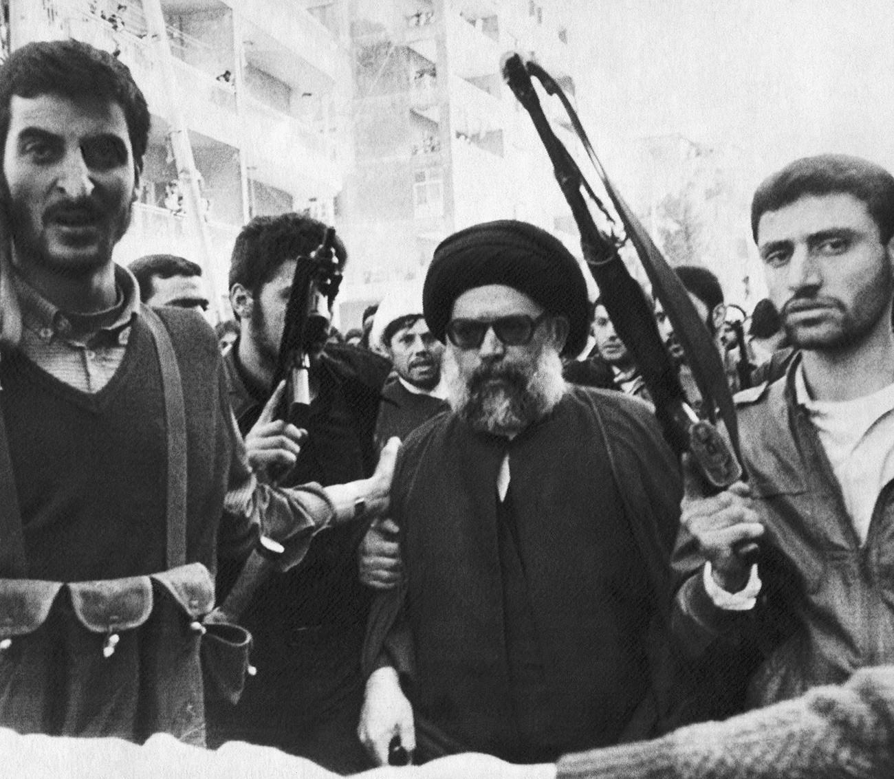 Мохамед Хюсеин Фадлала, заобиколен от охраната си  в южно предградие на Бейрут, Ливан, отива на погребалната церемония на 75-те жертви на експлозия на автомобилна бомба. 9 март 1985 г.