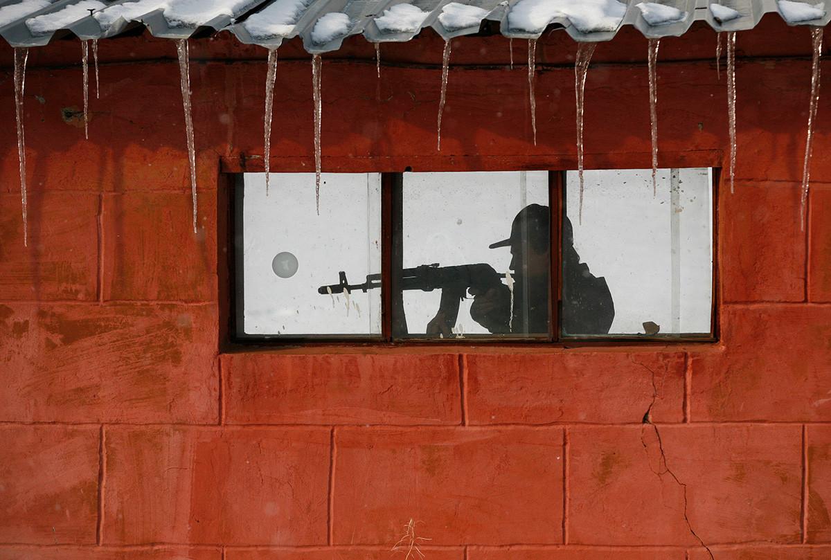 """Припадничката и конструкторката на специјалните единици на руската полиција Ирина Самит стрела од автоматот АК-47 """"Калашников"""" на тренинг во близина на градот Краснојарск, Русија."""