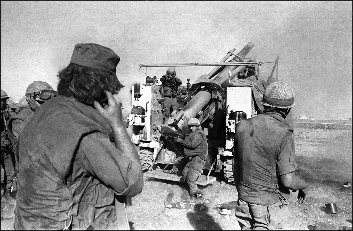 Israeli soldiers plug their ears as they fire shells from a French-made 155mm Howitzer gun at the Syrian lines on the Syrian Golan Heights, two weeks after the beginning of the Yom Kippur War, 17 October 1973.