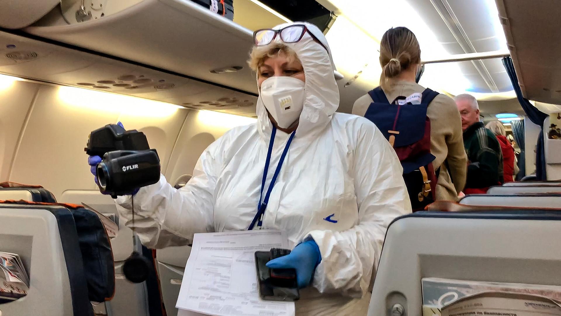 医者がシェレメチェヴォ空港に到着した飛行機で乗客の体温を測っている、2020年3月8日