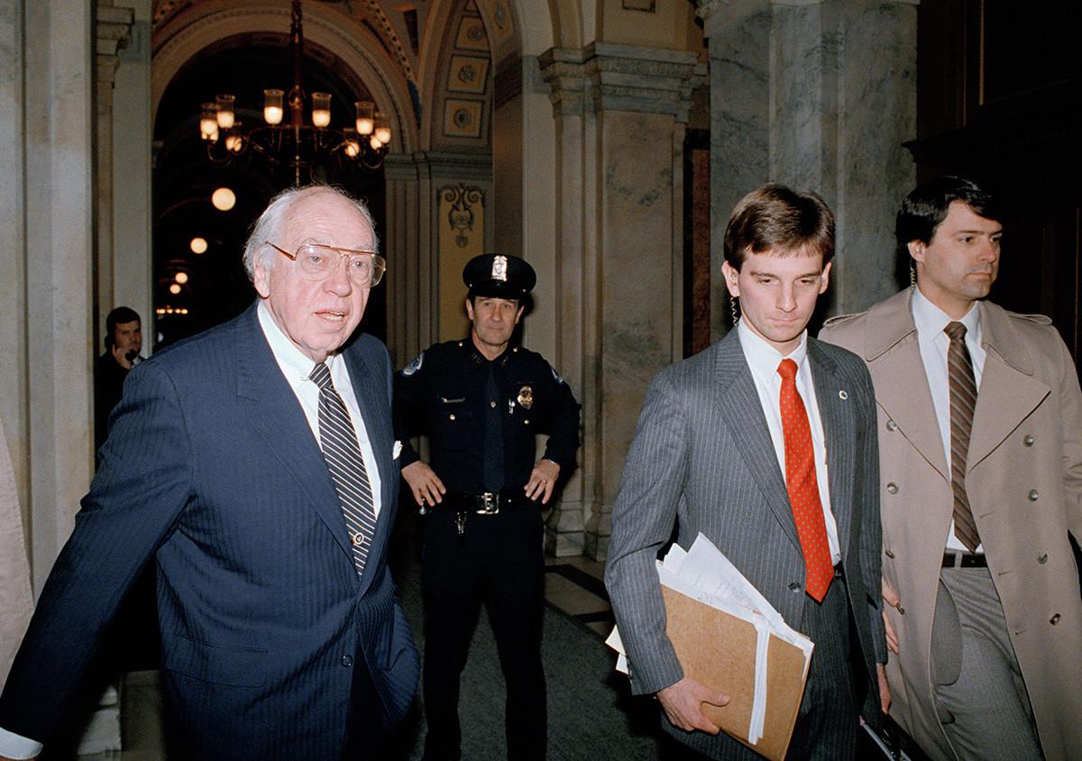 Direktur CIA William Casey berjalan melewati seorang polisi Capitol Hill pada Jumat, 21 November 1986.