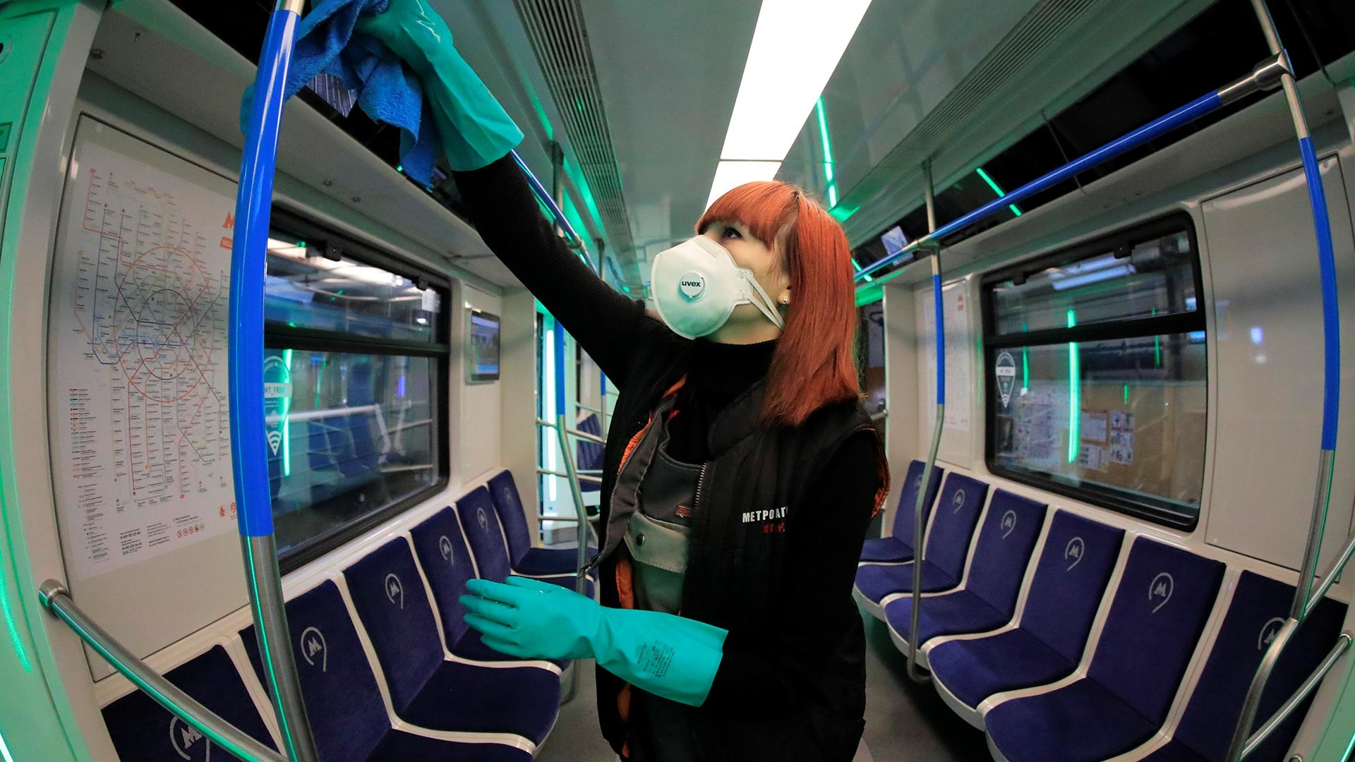 An employee wearing a protective face mask cleans and disinfects a subway train in Moscow