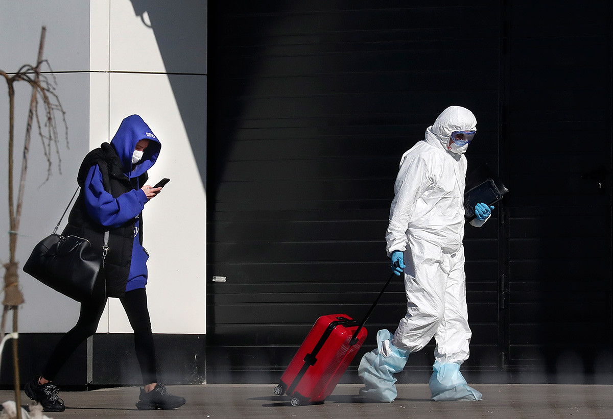 A medical worker helps a woman, suspected of having the coronavirus infection, with her suitcase to a hospital outside Moscow.