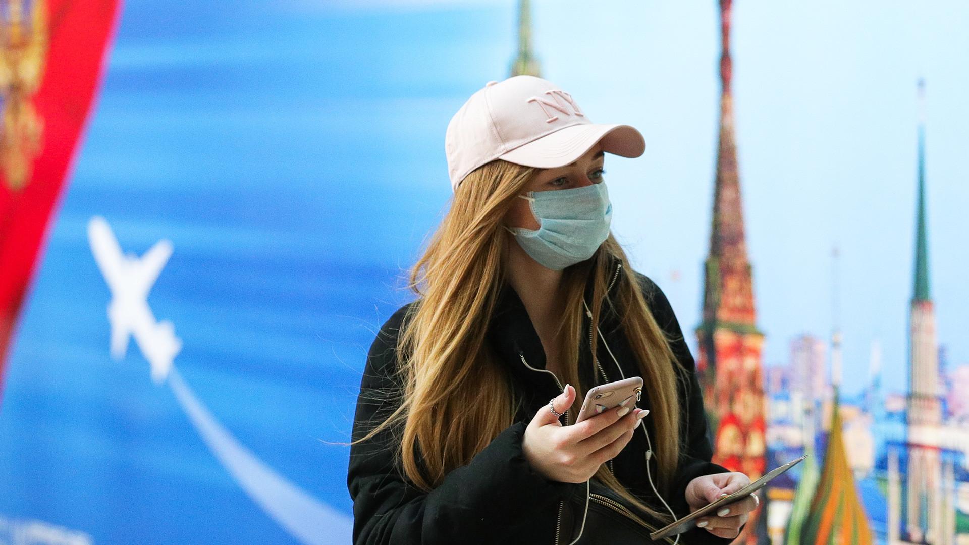 Seorang perempuan dengan masker di Bandara Internasional Sheremetyevo, Moskow.