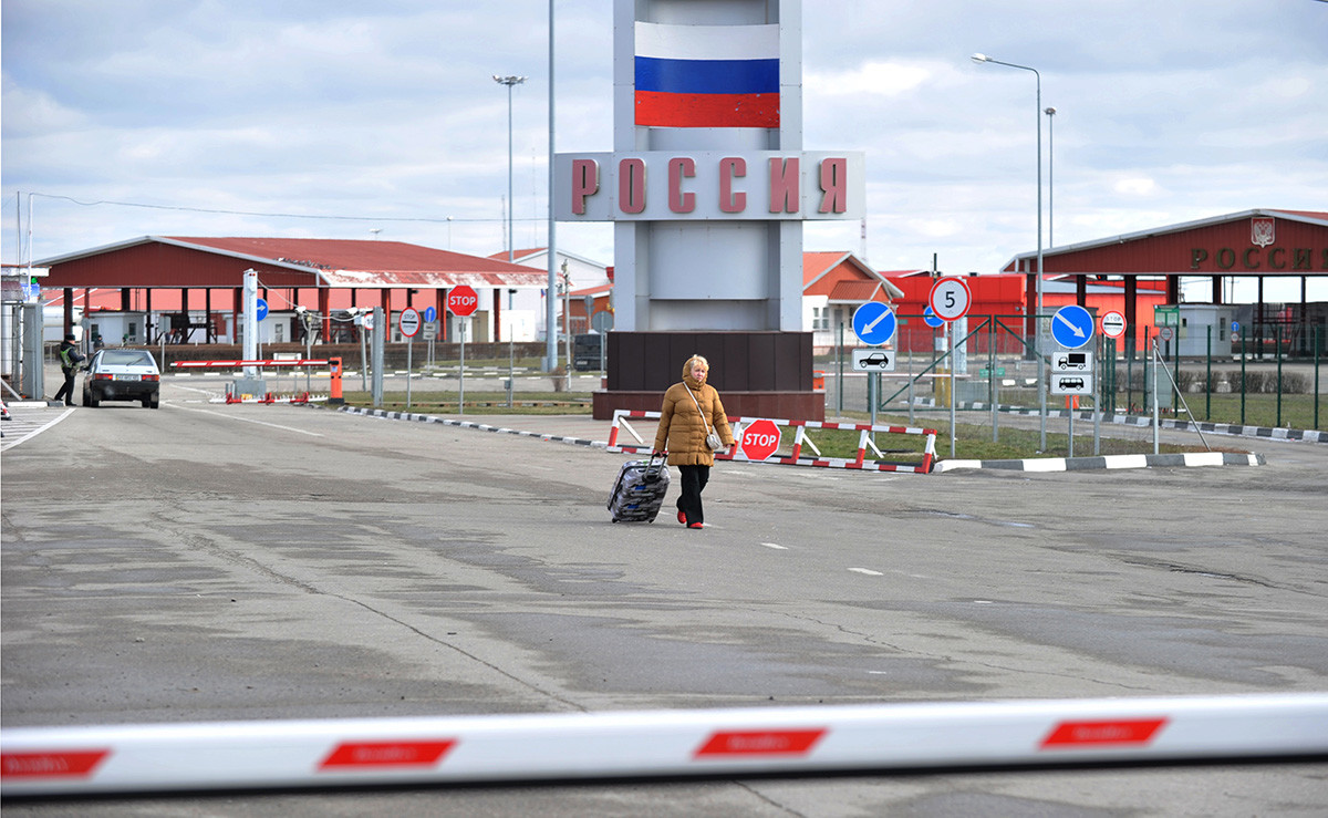 Seorang perempuan berjalan melewati pos pemeriksaan Goptivka, dekat Kharkiv, di perbatasan Ukraina-Rusia.