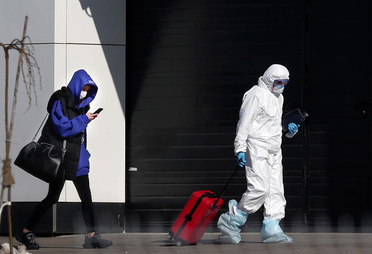 Seorang petugas medis membantu seorang perempuan, yang diduga terjangkit virus corona, dengan kopernya ke rumah sakit di luar Kota Moskow.