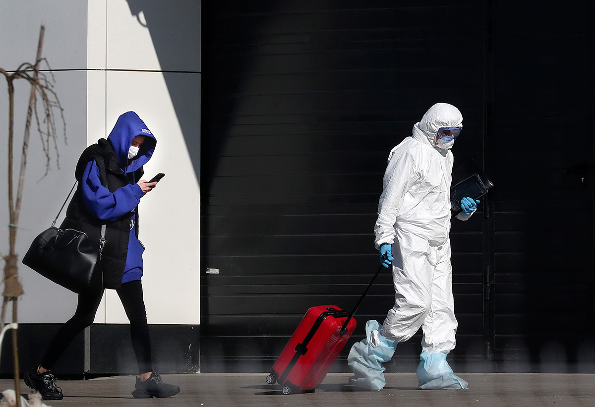 Medicinski radnik pomaže ženi za koju se sumnja da je zaražena koronavirusom s njezinim kovčegom da dođe do bolnice izvan Moskve.
