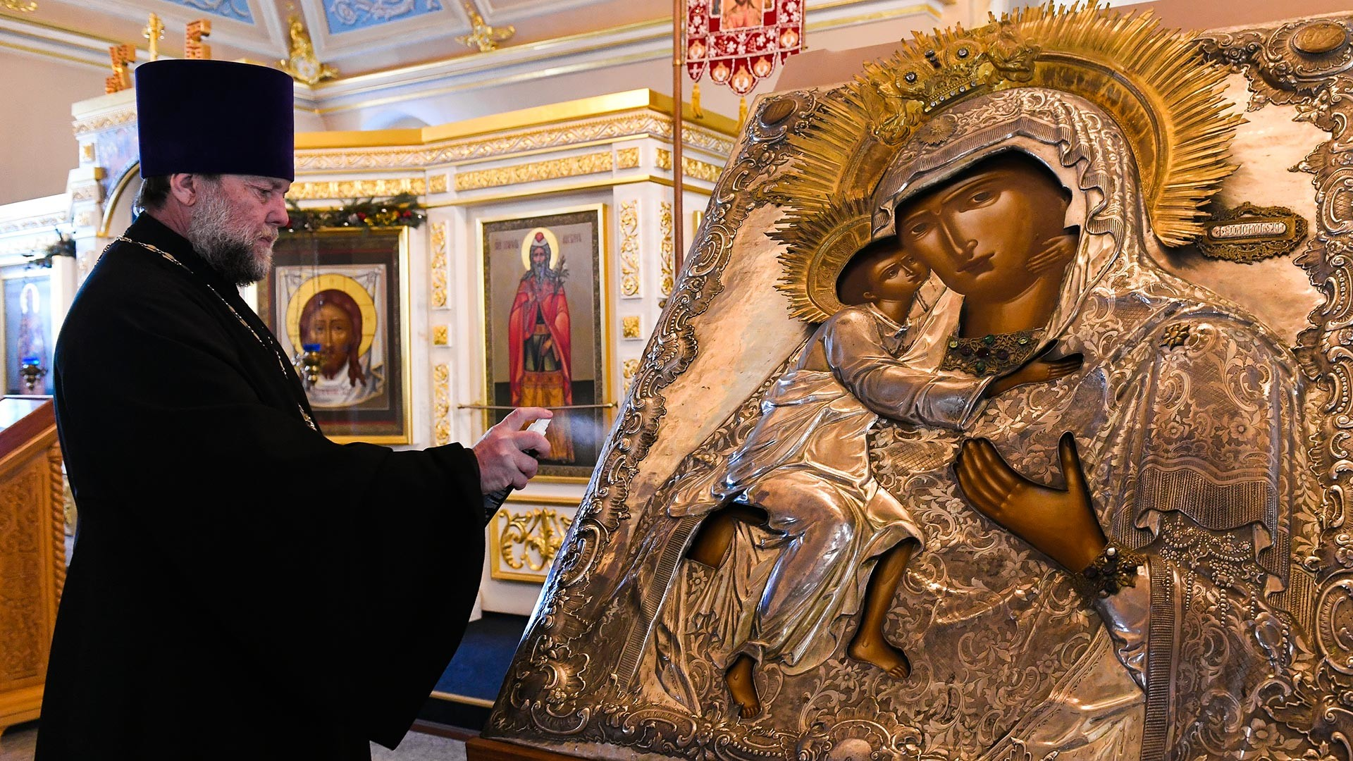 The rector of the Church, priest Vladimir Dukhovich during the sanitary treatment of the icon in the Church of St. Alexy in Rogozhskaya Sloboda
