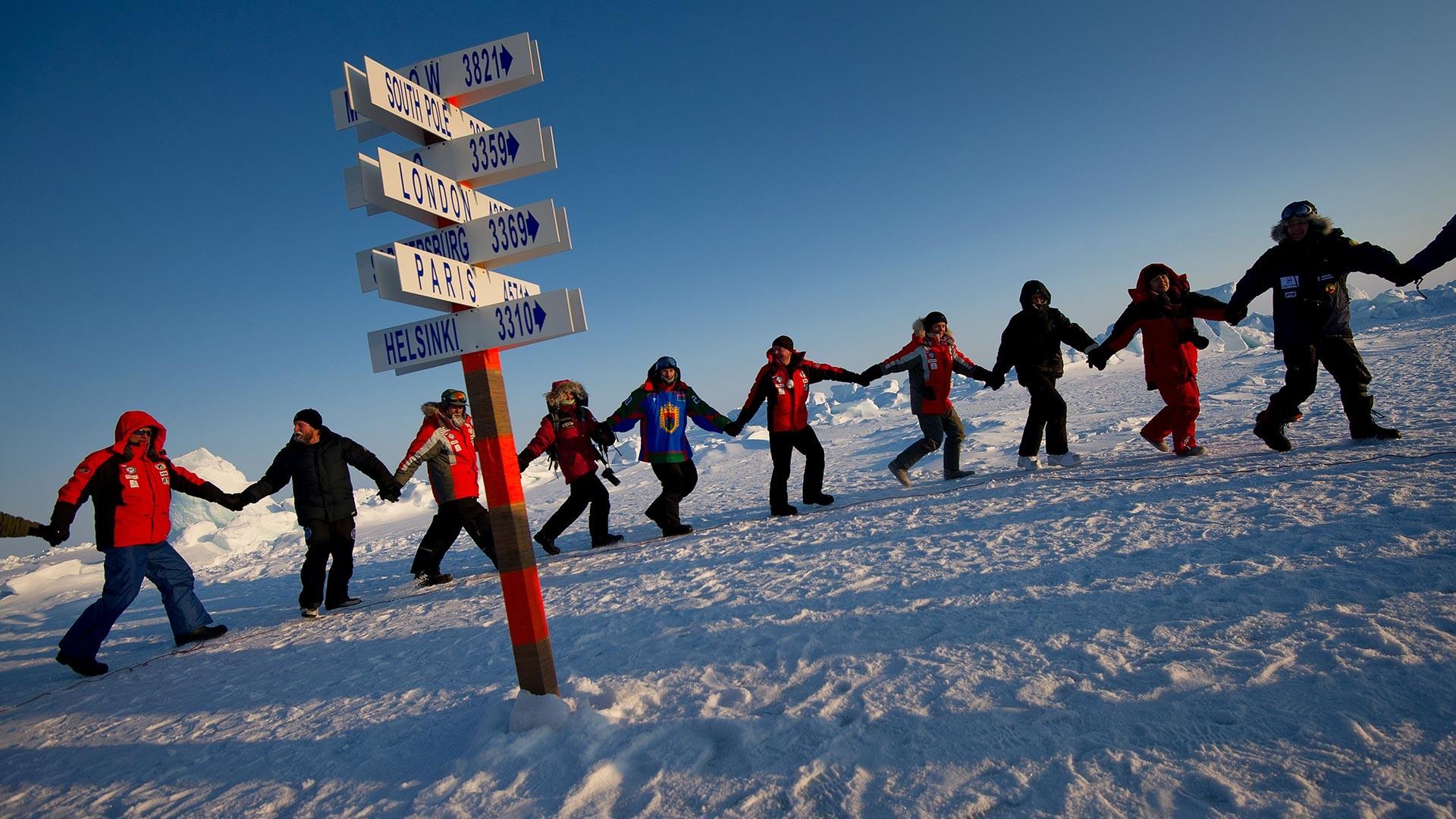Les participants de l'expédition Carélie – Pôle Nord – Groenland dansant autour du poteau symbolique désignant le Pôle Nord.