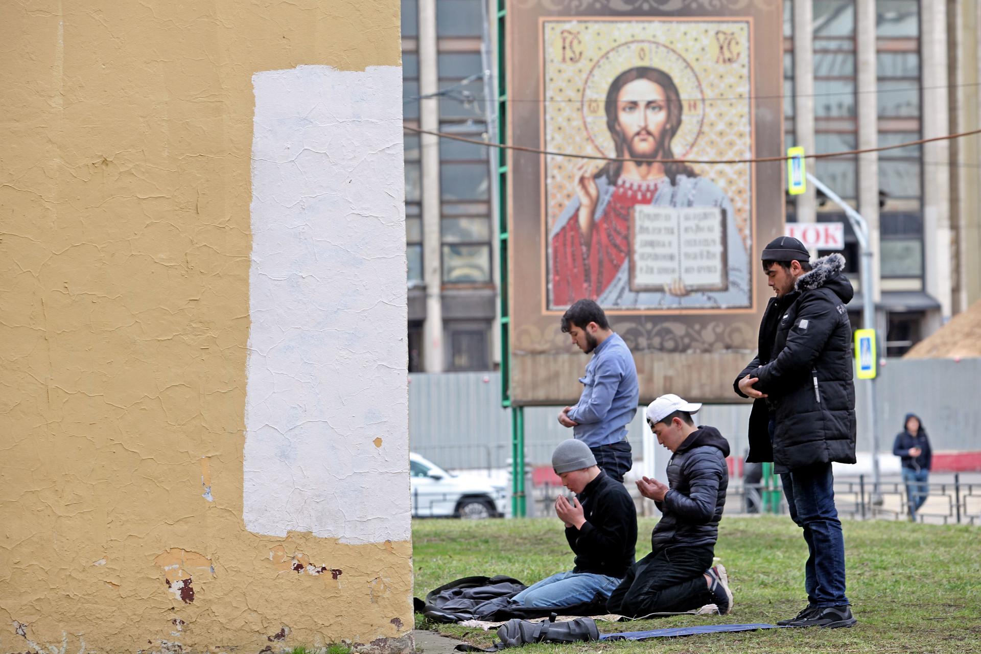 Umat Islam menunaikan salat Zuhur di taman, di depan gereja Ortodoks, tak jauh dari Masjid Agung Moskow, Jumat (20/3).