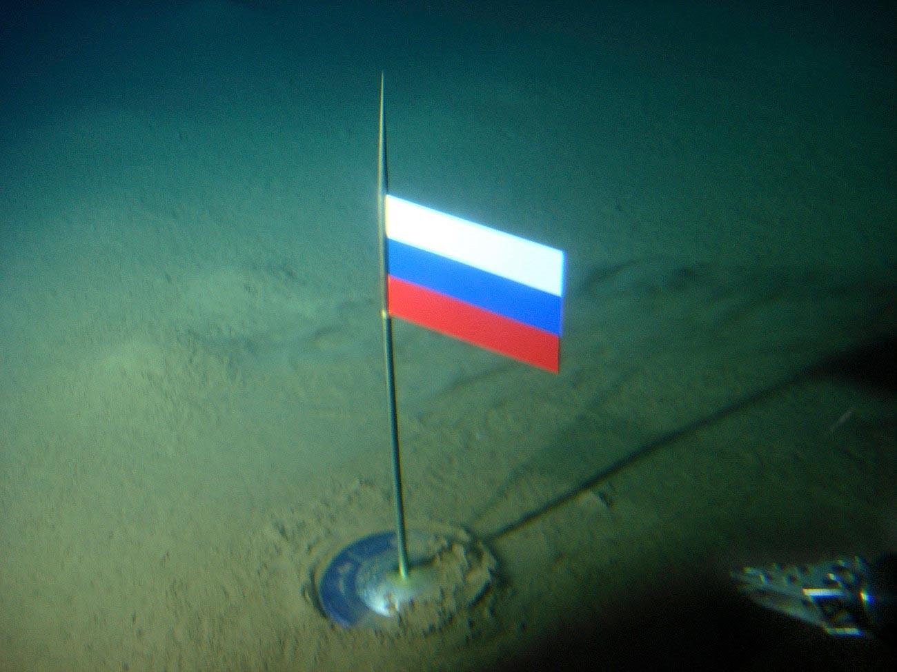 Zastava Rusije s kapsulom od titanija na dnu oceana ispod Sjevernog pola, nekoliko sekundi nakon što je 2. kolovoza 2007. godine postavljena pomoću batiskafa Mir-1.