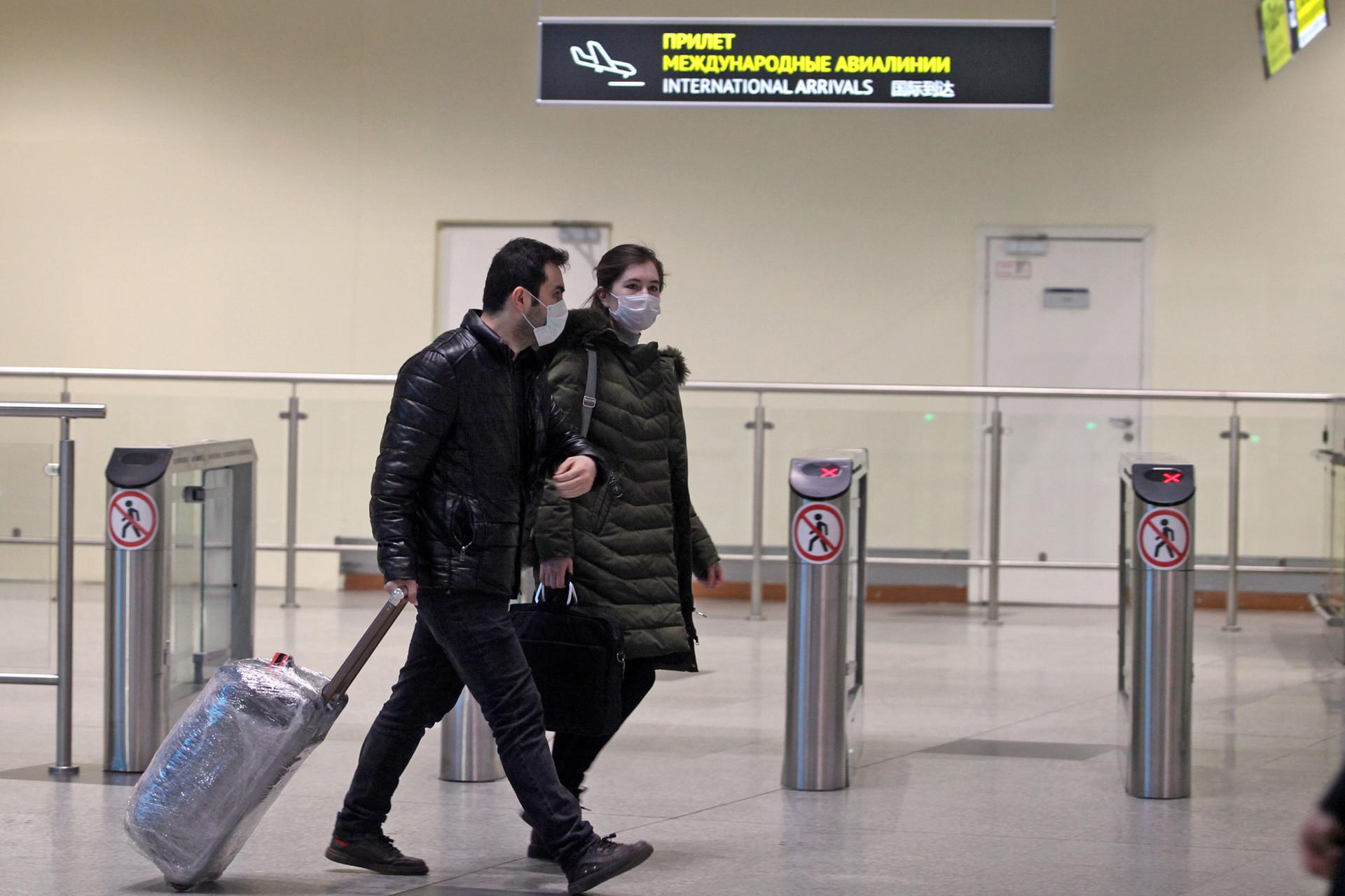 Dua penumpang melintas di dekat pintu kedatangan internasional pada hari pertama pemberlakuan pembatasan masuk warga asing di Bandara Internasional Domodedovo, Moskow, Rabu (18/3).