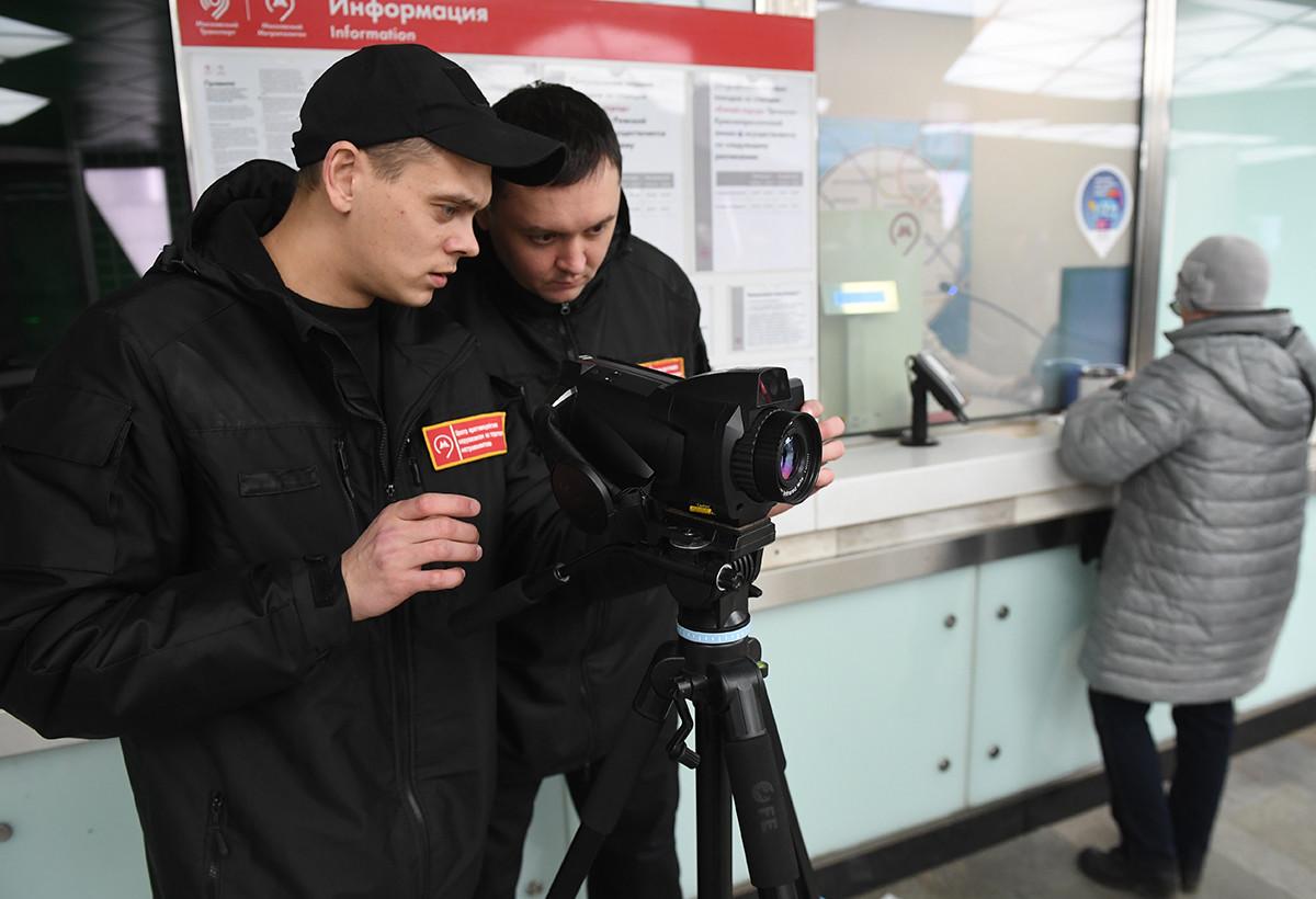 Сотрудники метрополитена проверяют у пассажиров московского метро температуру с помощью тепловизора.