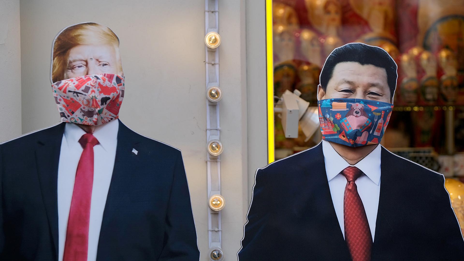Искројене картонске фотографије америчког председника Доналда Трампа и кинеског лидера Си Ђинпинга са маскама које се користе као превентива против заразе корона вирусом (COVID-19) испред продавнице сувенира у Москви, Русија, 23. март 2020.