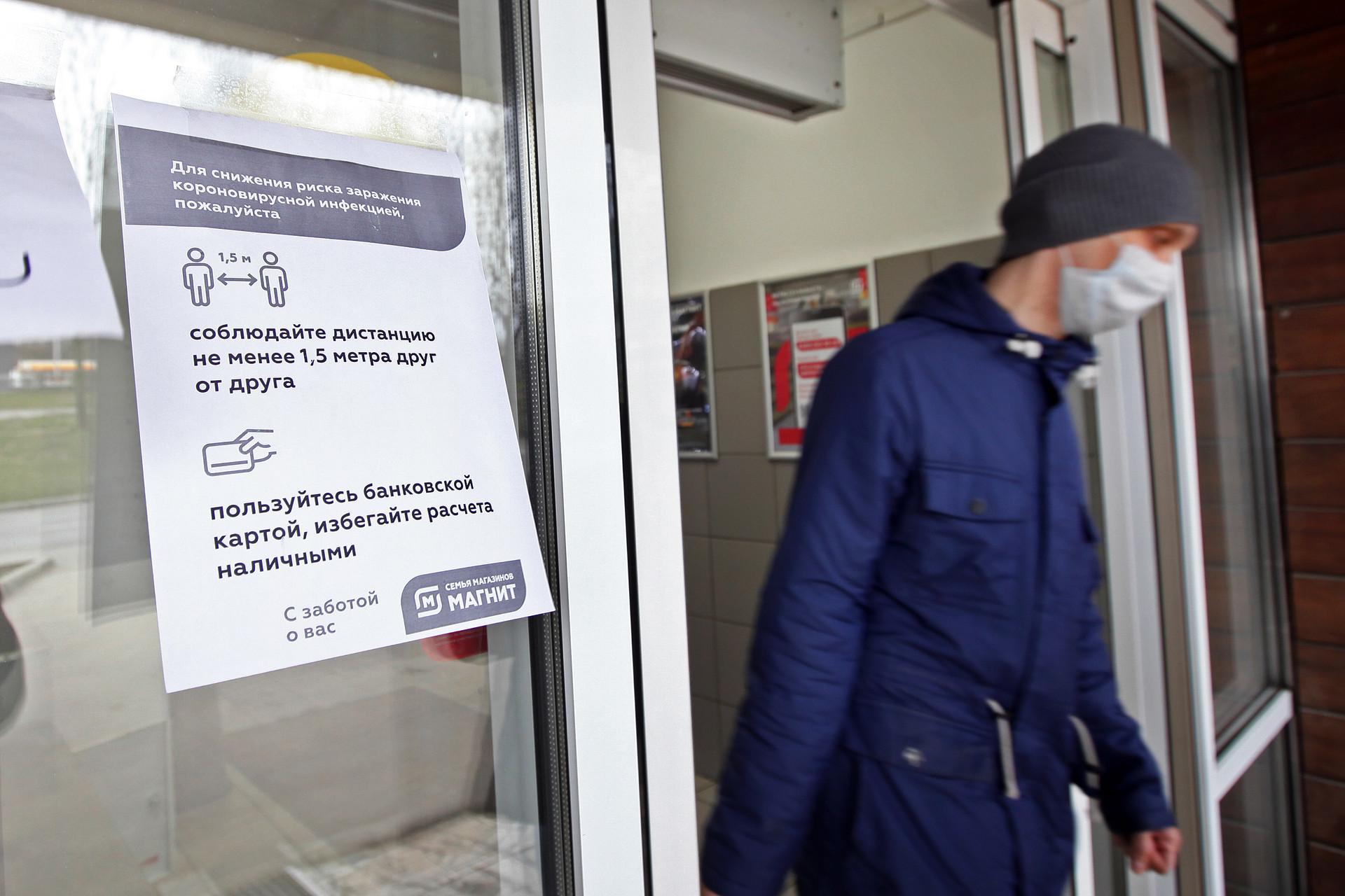 Pengumuman untuk menjaga jarak dan pembayaran menggunakan kartu ditempel di sebuah toko di Moskow, Senin (30/3)