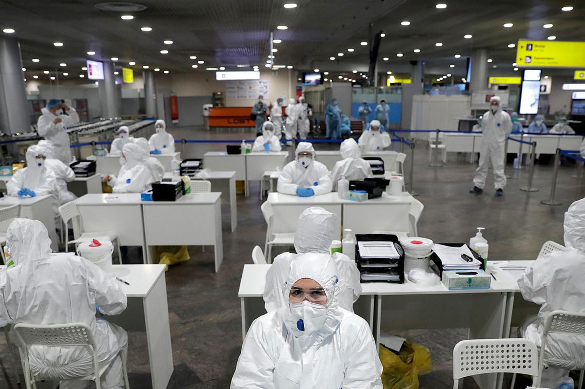Especialistas médicos russos aguardam passageiros que chegam de países estrangeiros para teste no aeroporto Sheremetievo, em Moscou
