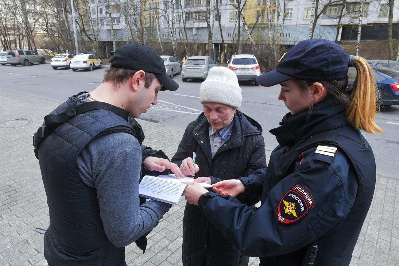 Guardas conversam com idosa em Moscou.