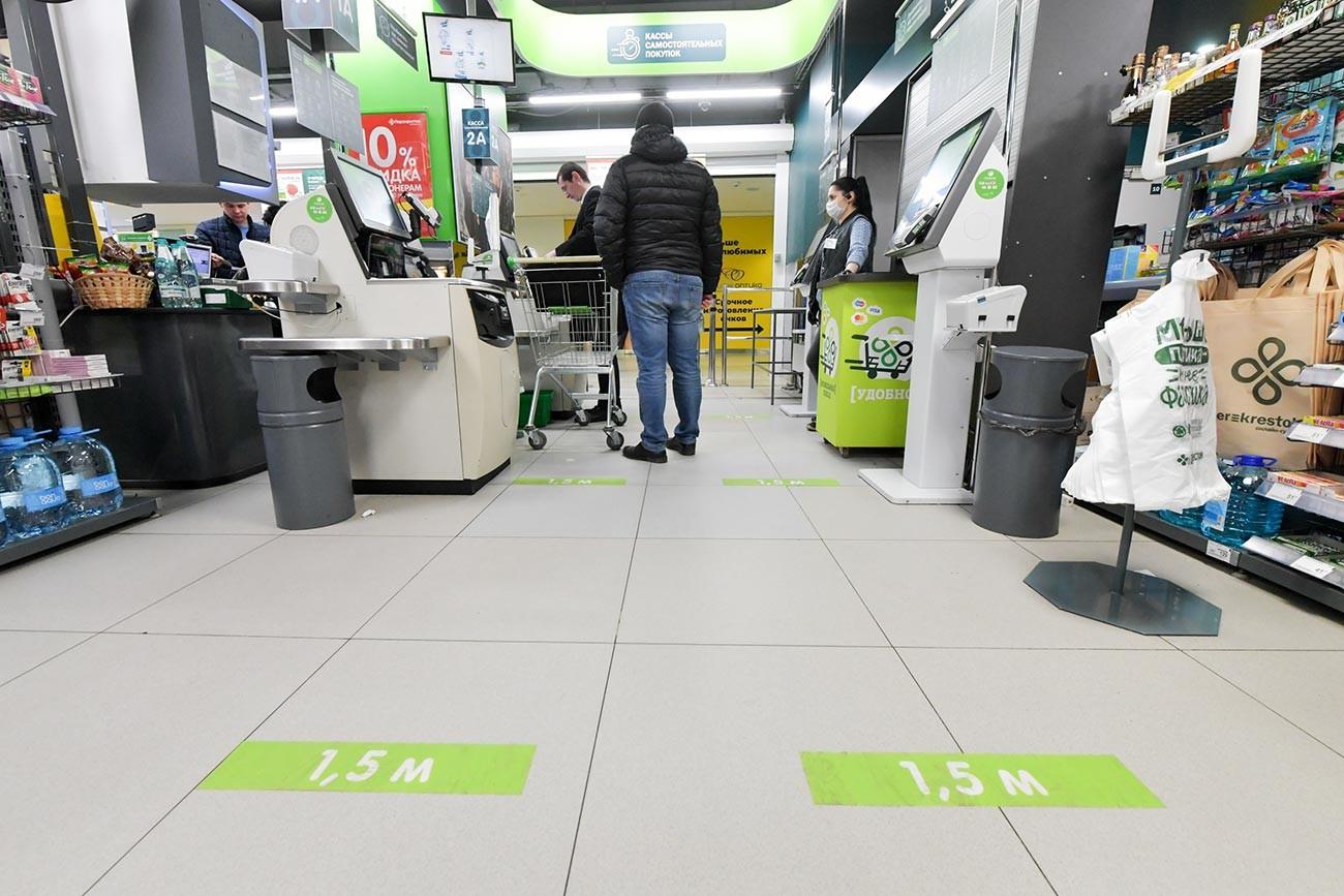 モスクワのスーパーは床にステッカーを張り、レジに並ぶ客が互いに1.5メートルの間隔を保てるようにされる。