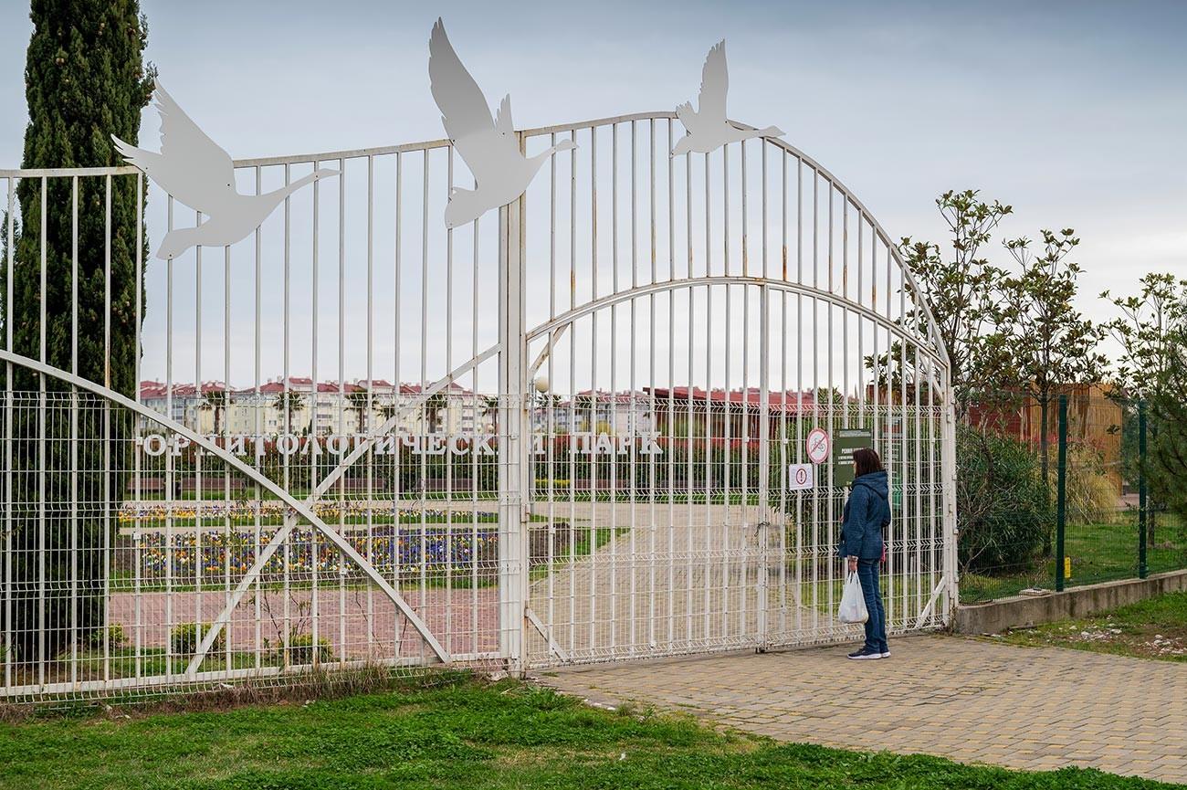 Mulher lê placa sobre fechamento de parque em Sôtchi devido à epidemia de coronavírus.