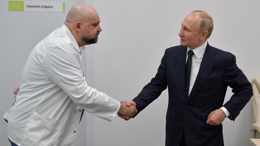 Kepala Dokter Rumah Sakit Kota No.40 Denis Protsenko berjabat tangan dengan Presiden Vladimir Putin seusai meninjau rumah sakit, Senin (24/3).