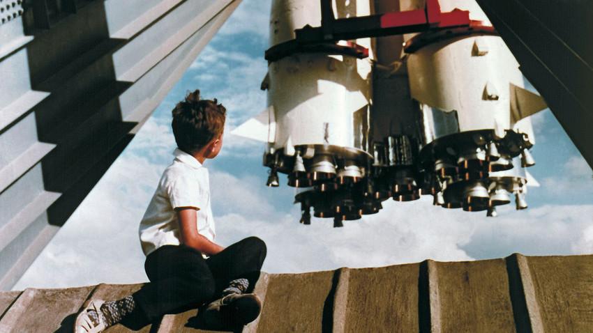 """Млад посетител на Изложбата на достигнувањата на народното стопанство на СССР седи на платформа пред ракета """"Восток"""" близу павилјонот """"Космос""""."""