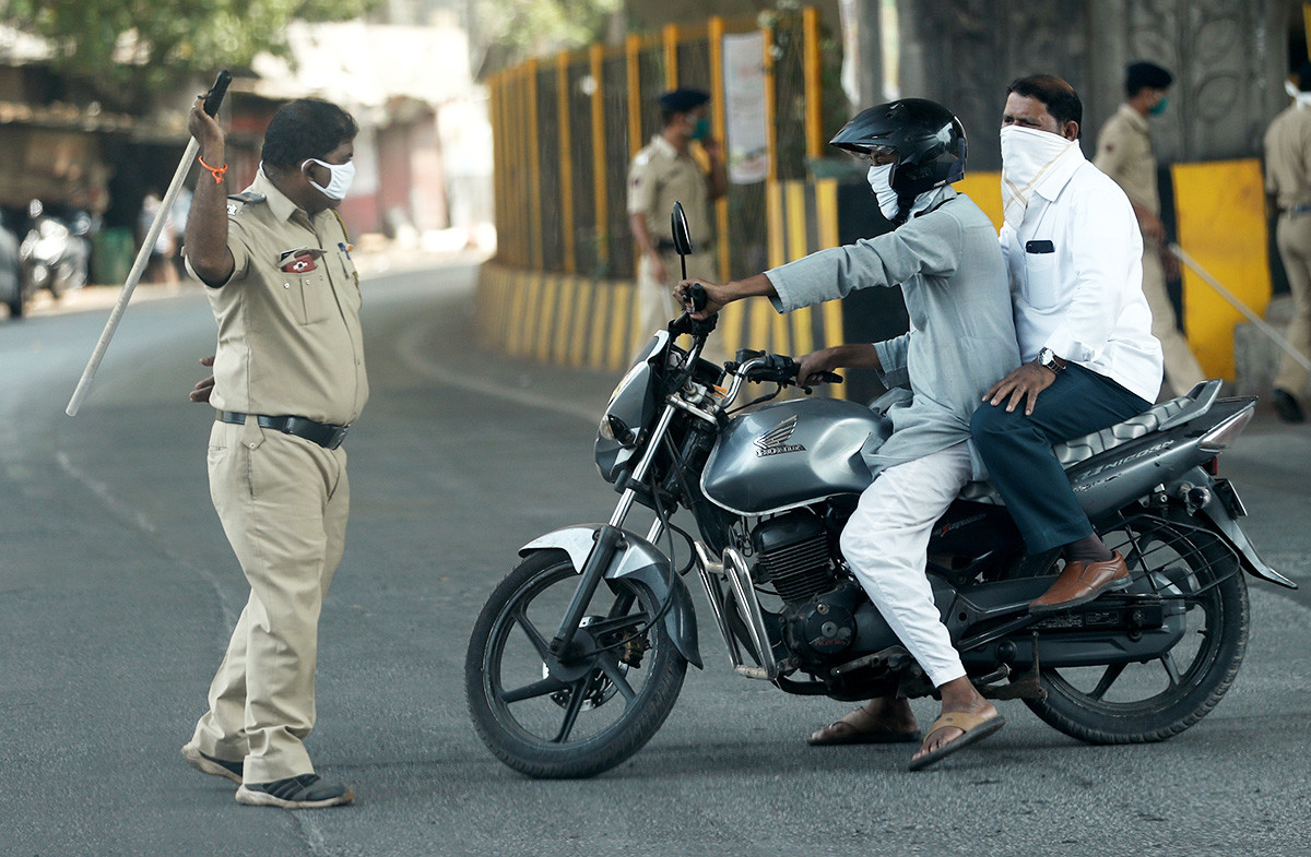A policeman wields his baton at a man riding a motorbike as a punishment for breaking the lockdown rules, after India ordered a 21-day nationwide lockdown to limit the spreading of coronavirus disease (COVID-19) in Mumbai, India