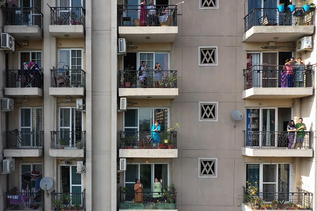 La gente se reúne en los balcones de un edificio residencial para aplaudir y agradecer a los proveedores de servicios esenciales durante cuarentena