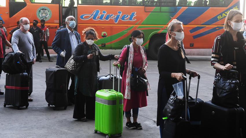 Extranjeros con máscaras medicas se alinean fuera de la terminal de salida del Aeropuerto Internacional Subhash Chandra Bose de Netaji para abordar un vuelo especial de evacuación