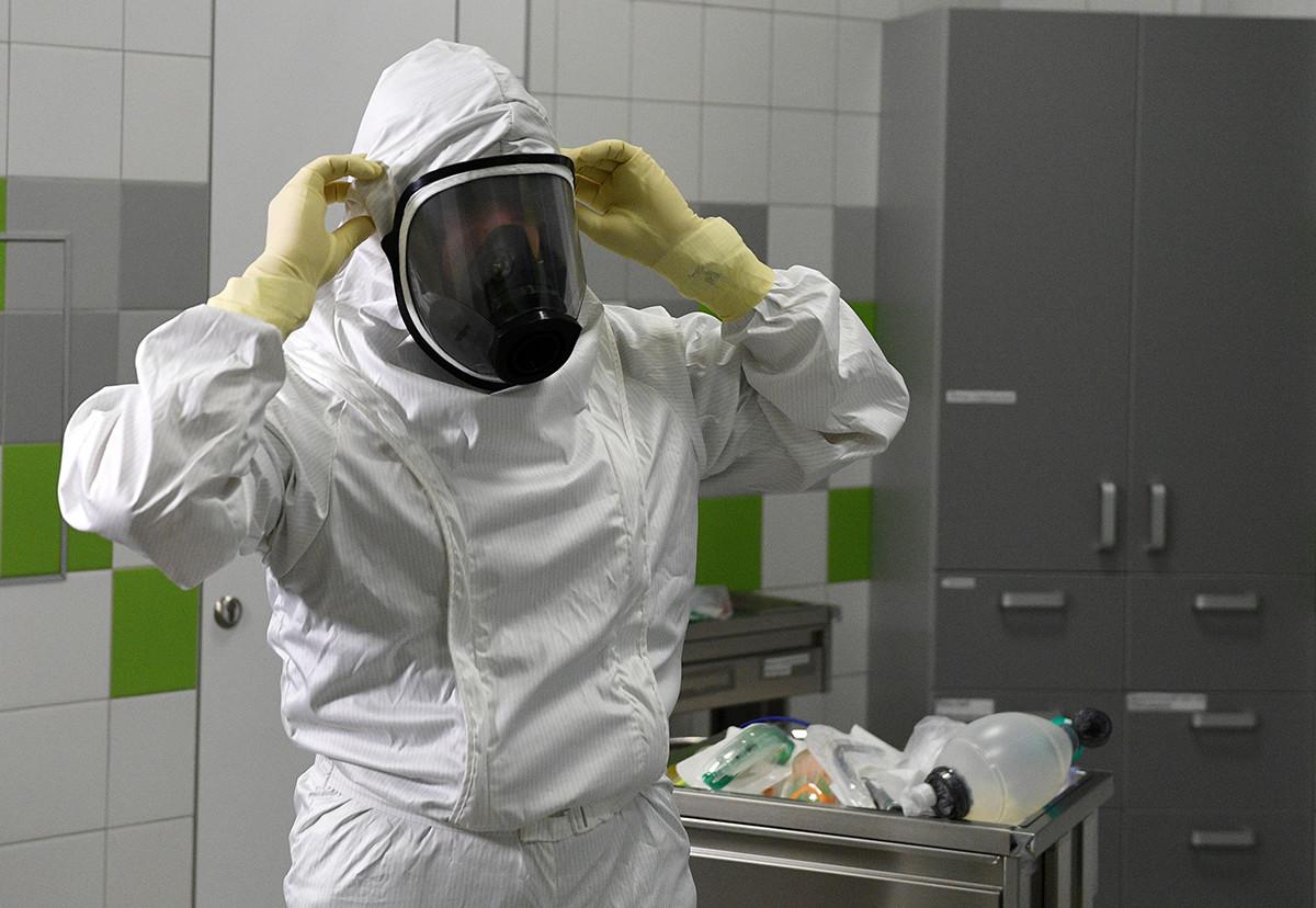 Врач надевает противочумный костюм в Ильинской больнице в Московской области.