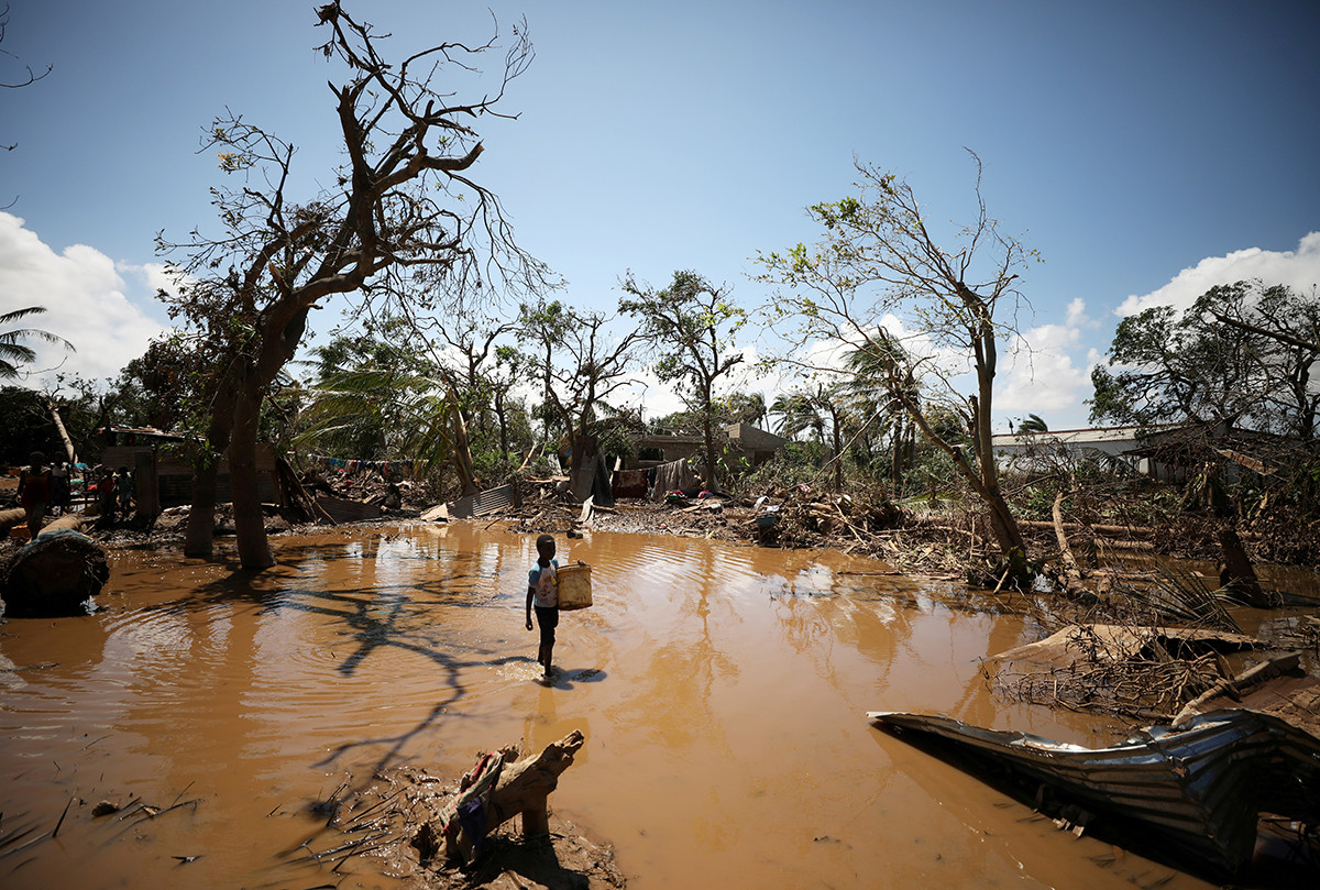 A child walks past debris as flood waters begin to recede in the aftermath of Cyclone Idai, in Buzi.
