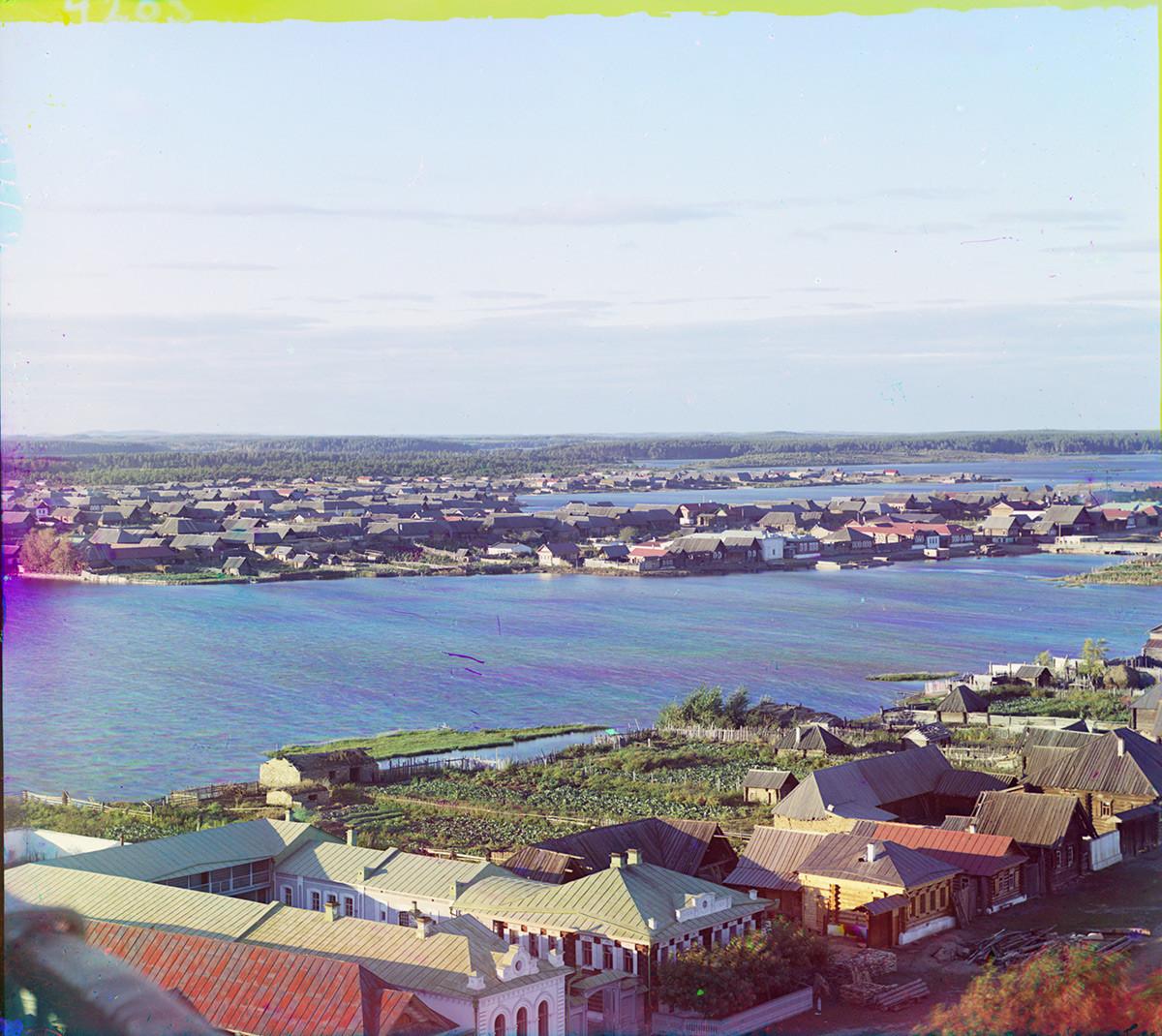 Kasli. Pogled na severozahod z tovarniškim ribnikom in jezerom Velike Kasli (v ozadju). Hiše z vrtnimi parcelami. Poletje 1909
