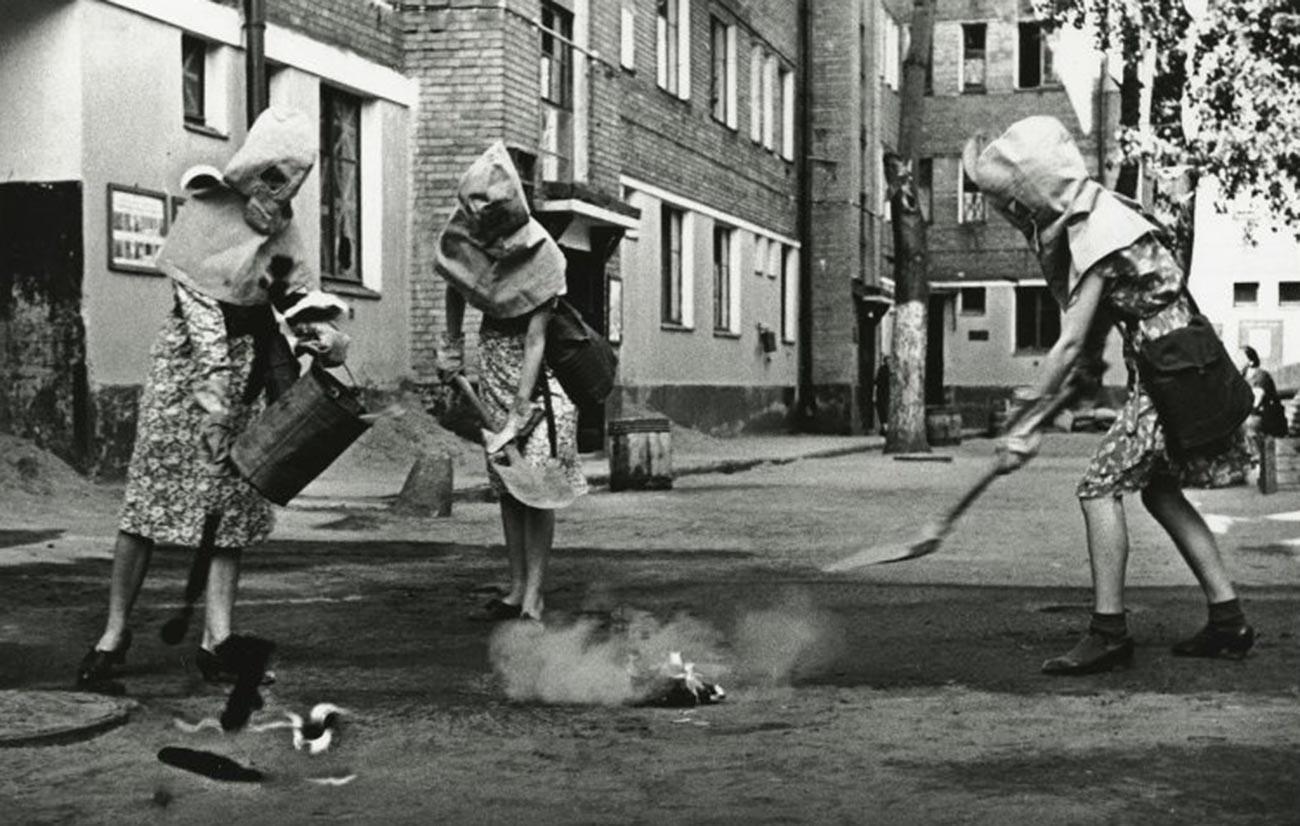 Нина Деева, Марина Никольская и Лиза Быстрова в специальных капюшонах на практическом занятии по тушению зажигательных бомб, 1941.