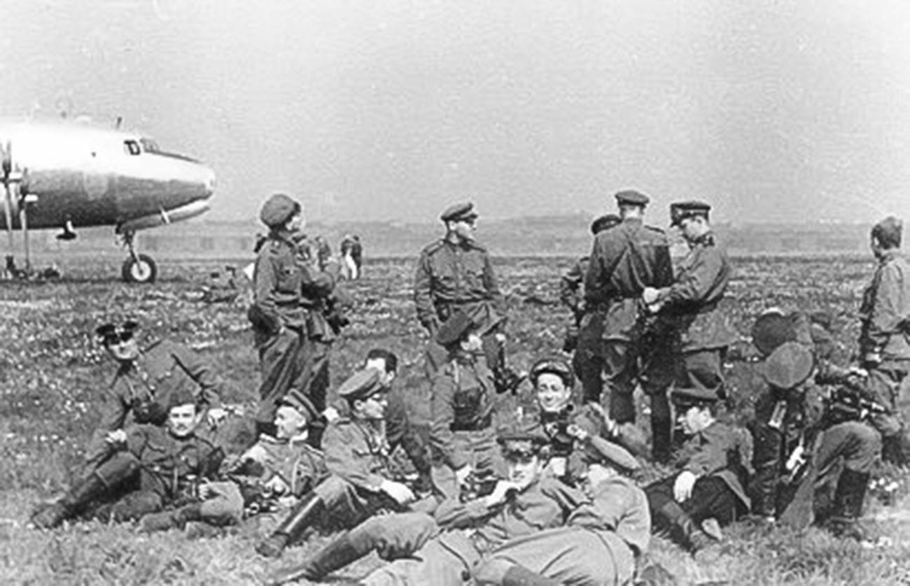 イリヤ・アロンス。ドイツの降伏文書に署名するためにやって来る連合国司令官らを待つ戦場カメラマンら。ベルリンのテンペルホーフ空港にて。1945年5月8日。
