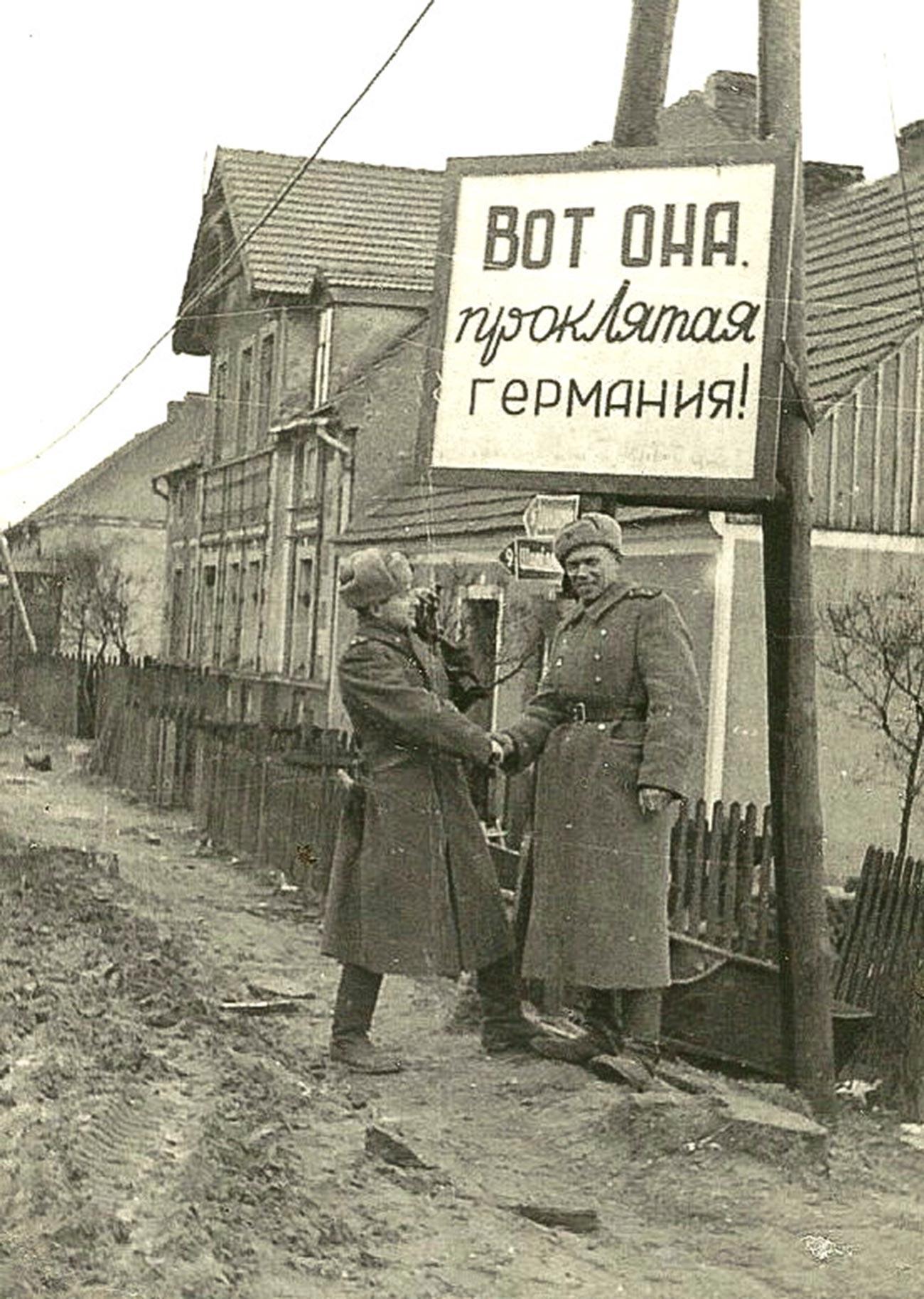 看板には「ここにいた、忌々しいドイツ!」の文言。『ポメラニアの戦い』を撮影中の戦場カメラマン、イリヤ・アロンス(左)とボリス・デメンチエフ。ポーランドとドイツの旧国境にて。1945年4月。