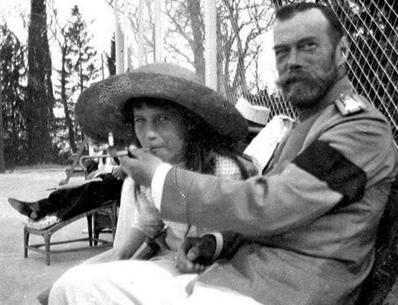 Nicholas II offers Anastasia a drag from his mouthpiece that holds a cigarette.