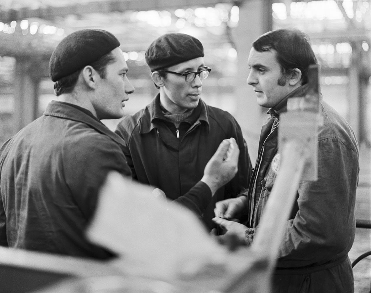 V hali za varjenje ogrodja tovarne VAZ; sovjetska specialista Sergej Jasinski in Nikolaj Borodin se pogovarjata z italijanskim specialistom Vittoriom Benagijem (z leve proti desni)