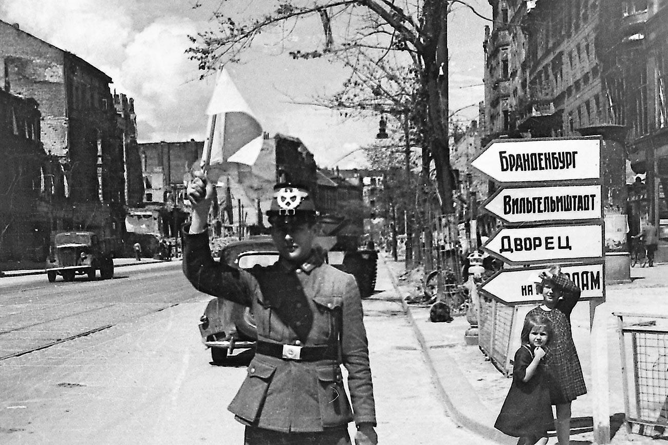 Un primer oficial alemán de tráfico comienza su servicio, reemplazando a las mujeres del Ejército Rojo que usaban banderas. Berlín de la posguerra, verano de 1945.