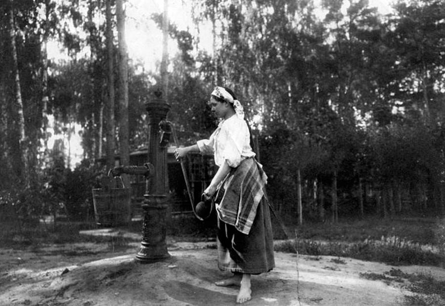 Garota diante de fontanário.