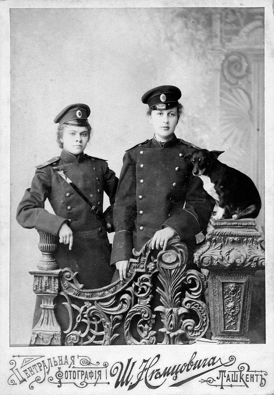 Duas amigas com uniformes militares e cachorro.