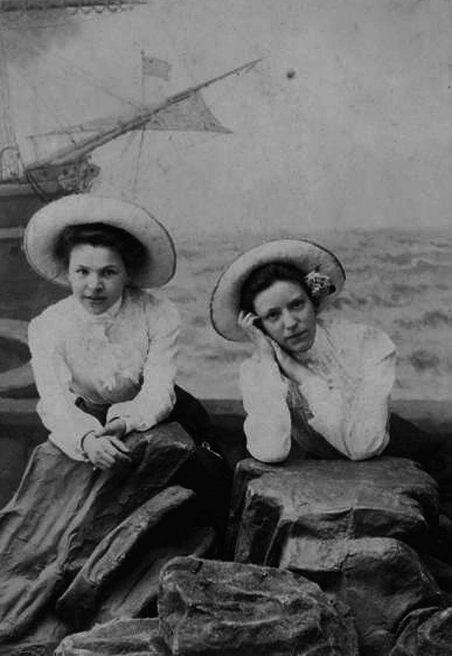 Two women posing in hats