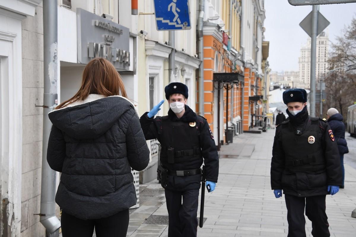 Des policiers contrôlant une passante à Moscou afin de déterminer toute infraction au confinement.
