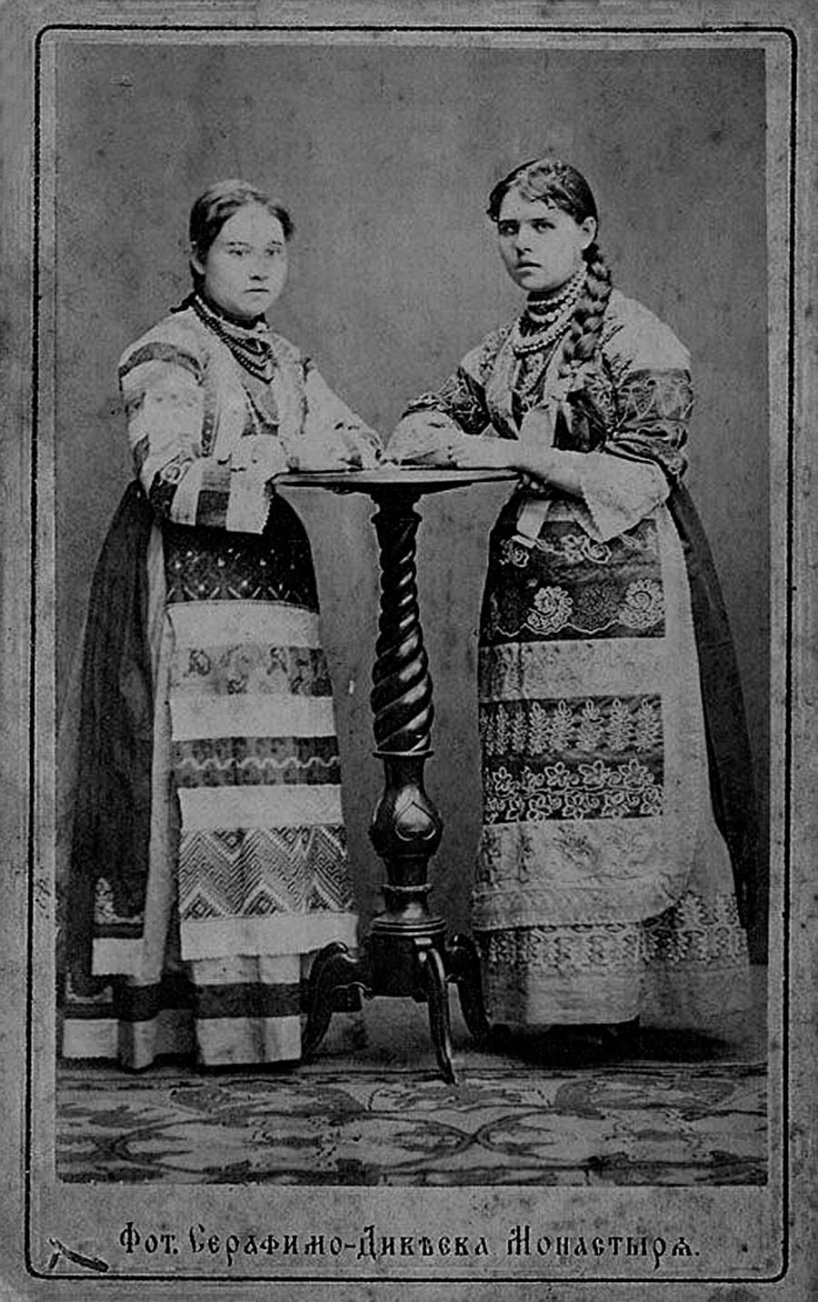 Dua perempuan mengenakan pakaian nasional Rusia.