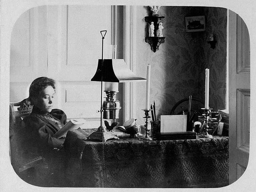 Seorang perempuan membaca buku di rumah.